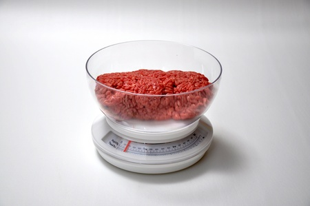 A pound of ground beef  is on a scale
