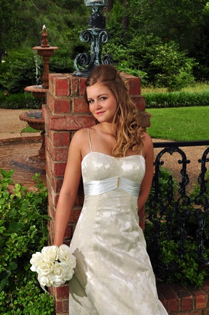 20 something: A 20 something Caucasian bride is leaning against a brick column holding her flowers. Stock Photo