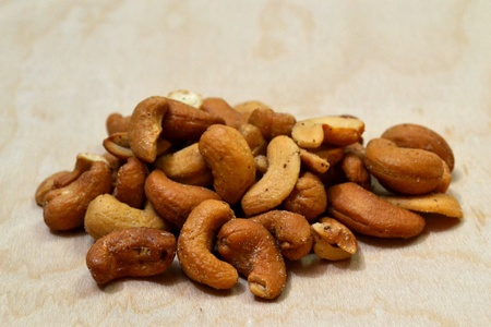 A pile of cashew nuts laying on a plain wood background. Stock Photo