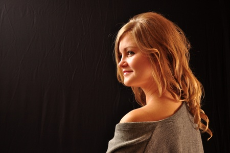 20 something: Profile of a young, 20 something Caucasian woman photographed on a black background Stock Photo