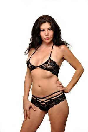 A attractive Caucasian lingerie model is posing in black lingerie. Stock Photo