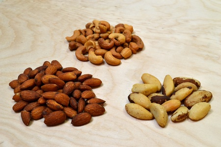 Three piles of nuts. One each of Almonds, Cashews, and Brazil nuts