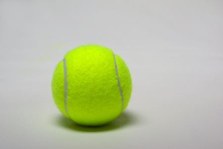 A green tennis ball sits on a plain white background. Imagens
