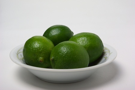 bowel: Four limes sit in a bowel on a plain white background.