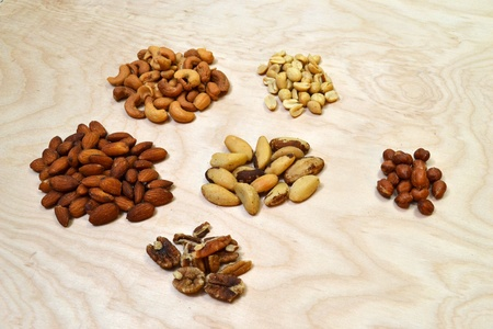 Six different piles of various types of nuts used in the making of mixed nuts.