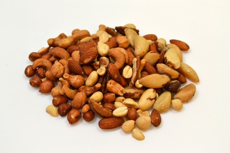 A plie of mixed nuts laying on a plain white background.
