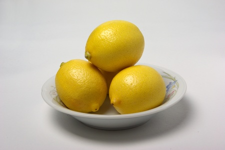 Four lemons sit in a small bowel on a plain white background.