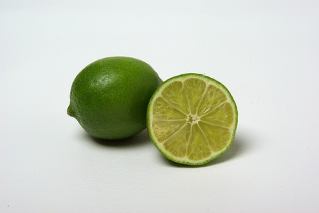A lime and a half of a lime sit on a white background