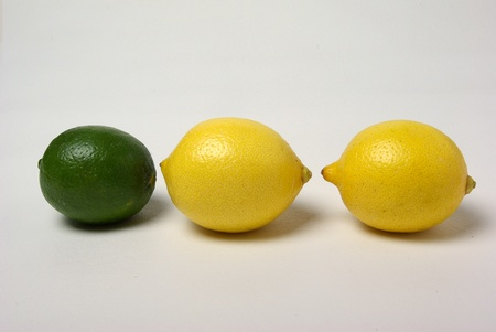 A lime and two lemons sit on a white background. Stock Photo