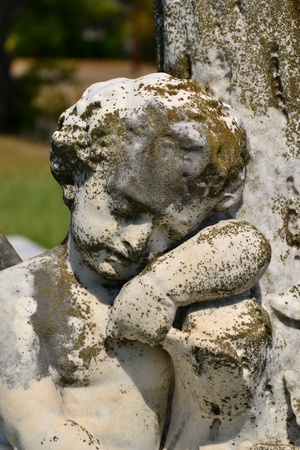A closeup of a small stone baby angel memorial photo