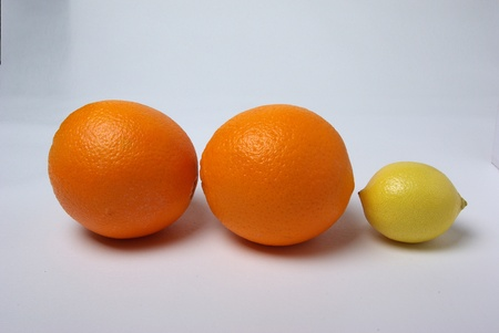 two oranges and a lemon sit on a white background.