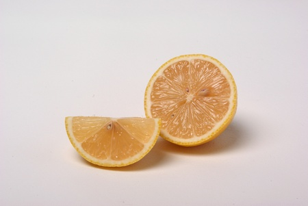 A whole lemon and a quarter of a lemon sit on a white background.