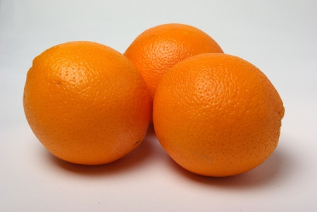 Three oranges are sitting on a white background. Stock Photo