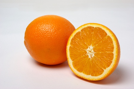A whole orange and a part of a orange sits on a white background. Stock Photo