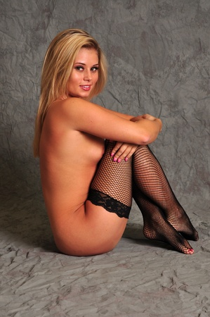 black stockings: A young attractive model is posing on a gray background while wearing black stockings Stock Photo