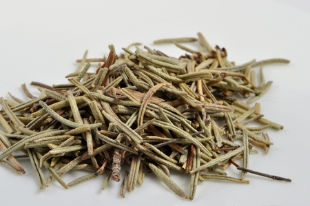 A pile of rosemary leaves sits on a plain white background.