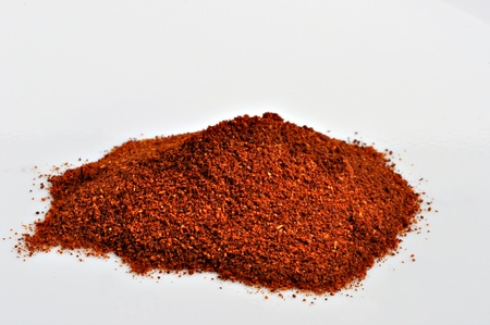 A smill pile of Paprika sits on a plain white background