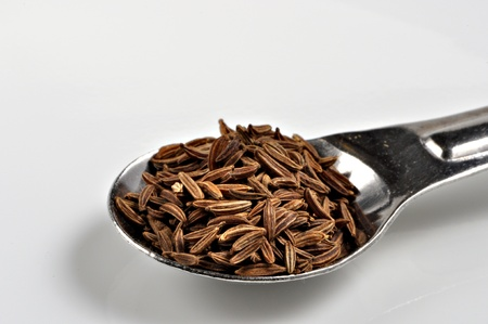 caraway: A spoonful of caraway seeds sits on a white background. Stock Photo