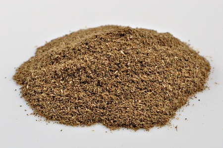 A small pile of ground thyme sits on a white background. Stock Photo