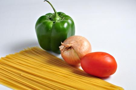 스파게티 파스타, 후추입니다. 양파와 토마토는 평범한 배경에 왕성한 식사로 결합되기를 기다리고있다. 스톡 콘텐츠