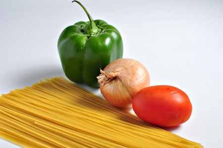 Spaghetti pasta, pepper. onion and tomato are waiting on a plain background to be combined into a hearty meal.