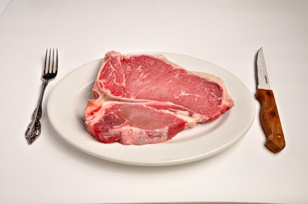 A raw t-bone steak is laying on a white plate on a white background.