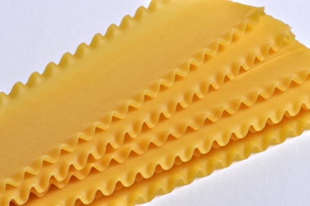 Dry lasagne pasta sits on a plain background.