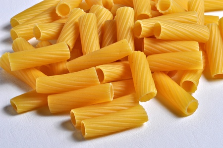 A pile of rigatoni pasta sits on a plain background.