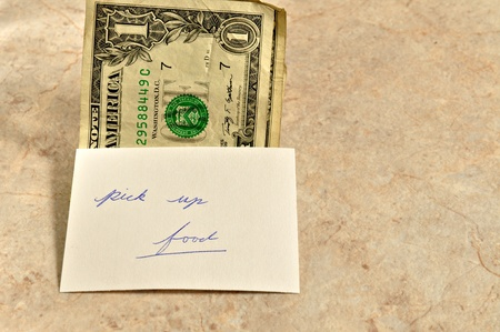 A few dollars on a table with a note to pick up food.