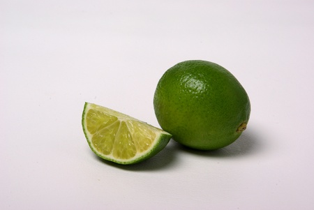 A whole lime sits beside a quarter piece of Lime Stock Photo