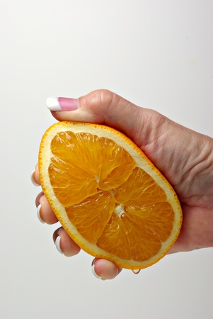 A closeup of a hand squeezing a orange for orange juice.