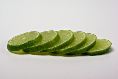 Lime slices lay on a plain background. Stock Photo