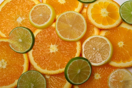 citric: Lime, lemon and orange slices sit on a plain background Stock Photo