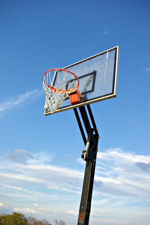 A basketball goal with the sky for a background out in the country.