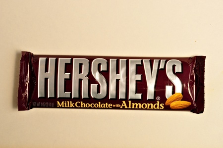 hershey's: A Hersheys milk Chocolate with Almonds candy bar sits on a white background.