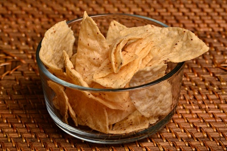 A small dish of corn chips sits on a wicker mat.