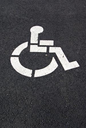 A white handicap parking symbol is painted on a black pavement.