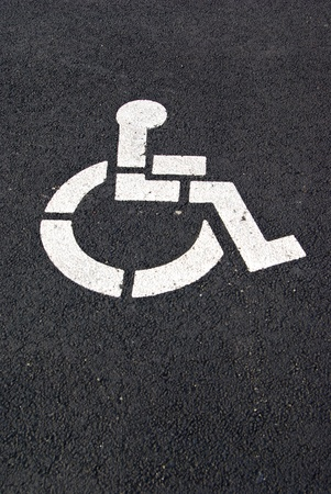 A white handicap parking symbol is painted on a black pavement.