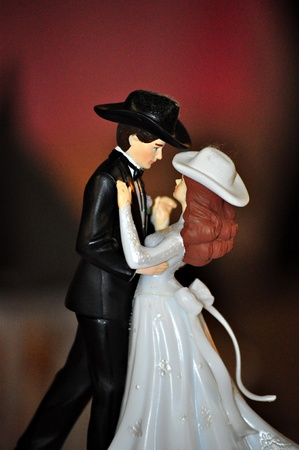 A wedding cake topper with a counry and western style sits ontop of a wedding cake. Фото со стока