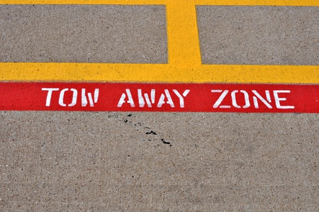 A painted tow away zone sign is painted on cement parking lot. Stock Photo