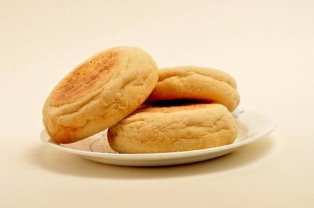 3 Engels muffins zitten op een kleine schotel op een effen achtergrond.