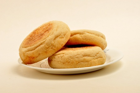 3 English muffins sit on a small saucer on a plain background. Фото со стока