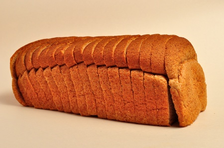 A loaf of wheat bread is laying on a plain background