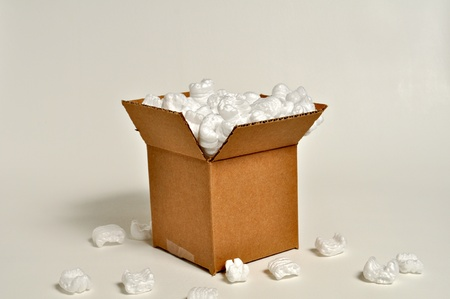 A cardboard box sits on a white background with shipping peanuts spilling out onto the ground.