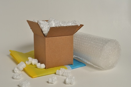 A brown cardboard box sits among bubble wrap, tissue paper and shipping peanuts Stock Photo
