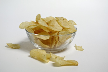 Potato chips sit in a glass bowl on a plain white background. Stock Photo - 12247120