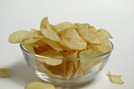 Potato chips sit in a glass bowl on a plain white background. Stock Photo - 12247121
