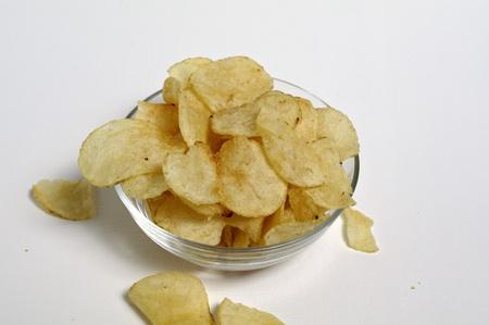 Potato chips sit in a glass bowl on a plain white background. Banco de Imagens