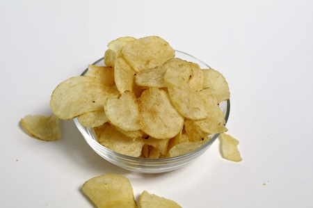 Potato chips sit in a glass bowl on a plain white background. Stock Photo - 12247126