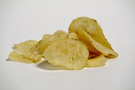 A pile of plain potato chips sits on a plain background